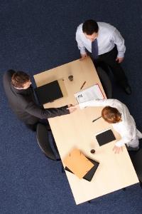 покупатель и продавец жмут друг другу руки в присутствии посредника